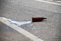 Exploding bottle of carbonated water rolling. On the road Royalty Free Stock Photo