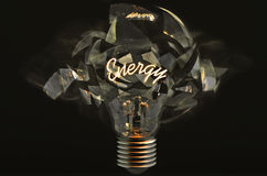 Exploding bulb. A light bulb with the glowing word Energy and a black background that is exploding Royalty Free Stock Images