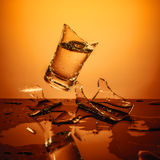Exploding Glass cup with water shattering over orange background. Royalty Free Stock Photos