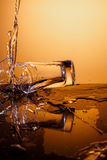 Exploding Glass cup with water shattering over orange background. Exploding Glass cup with water shattering over orange background, crash and splashes Royalty Free Stock Images