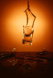 Exploding Glass cup with water shattering over orange background. Royalty Free Stock Image