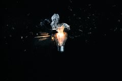 Exploding light bulb. Lightbulb exploding and inside visible smoke and sparks royalty free stock images