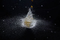 Exploding water balloon. An exploding yellow party balloon filled with water Stock Image