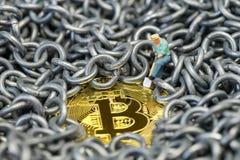 Exploitation de Bitcoin par le chiffre miniature tenant la pelle creusant sur le shi Images libres de droits