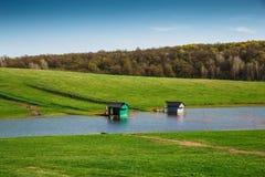Exploitation de pisciculture au petit lac ou à l'étang artificiel pour le poisson d'eau douce d'élevage parmi les prés verts Photo libre de droits