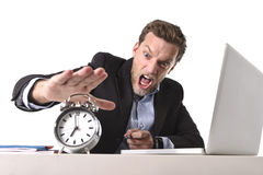 Exploited businessman at office desk stressed and frustrated with  alarm clock in out of time and deadline concept. Young angry exploited businessman at office Royalty Free Stock Images