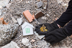 Exploiter thief loots a house devastated by earthquake. Thief with black gloves steals gold and jewels from a house destroyed by earthquake stock photography