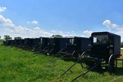 Exploração agrícola com um grupo de carrinhos estacionados de Amish em um campo fotografia de stock