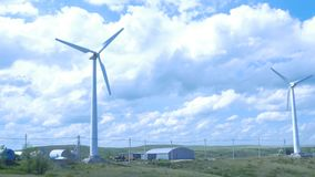 Exploração agrícola das turbinas de vento moinho de vento do aerogenerator no dia ensolarado do céu azul Turbinas de vento no cam Imagens de Stock
