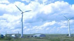 Exploração agrícola das turbinas de vento moinho de vento do aerogenerator no dia ensolarado do céu azul Turbinas de vento no cam Fotos de Stock