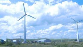 Exploração agrícola das turbinas de vento moinho de vento do aerogenerator no dia ensolarado do céu azul Turbinas de vento no cam Fotografia de Stock Royalty Free