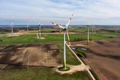 Exploração agrícola das turbinas de vento no por do sol na mola Imagens de Stock Royalty Free