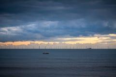 Exploração agrícola de vento a pouca distância do mar no horizonte na última luz do dia imagens de stock