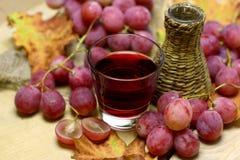 A exploração agrícola fez a vinhos a garrafa e uvas de vime Fotografia de Stock