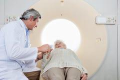 Exploración de Comforting Patient Before CT del radiólogo Fotos de archivo libres de regalías