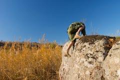 Explorador Climbing en roca grande en el campo Imagen de archivo libre de regalías