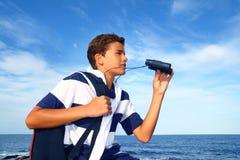 Explorador de los prismáticos del adolescente del muchacho en playa azul Fotografía de archivo libre de regalías
