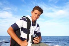 Explorador de los prismáticos del adolescente del muchacho en playa azul Fotos de archivo