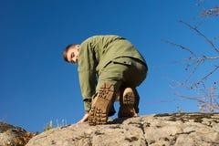 Explorador de muchachos Climbing en roca mientras que mira el suyo detrás Imágenes de archivo libres de regalías