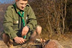Explorador de sexo masculino blanco joven Cooking Sausages en la tierra Imagenes de archivo