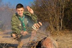Explorador que saluda sus salchichas de cocinar Fotografía de archivo libre de regalías