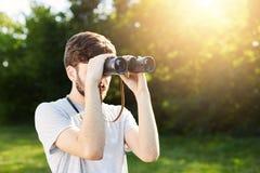 Explorador turístico joven que mira a través de los prismáticos en lugares desconocidos de exploración de la distancia Viajero qu Foto de archivo libre de regalías
