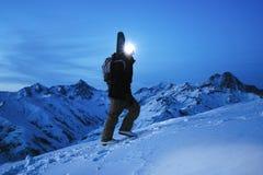 Explorador valiente con el faro y la mochila y una snowboard detrás el suyo subida trasera en la gran montaña nevosa en la noche  Imagen de archivo libre de regalías