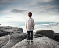 Exploration. Child observing the sea in front of him Stock Photos