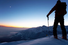 Exploration. At dusk a brave backcountry skier reaching the summit of the mountain after a long day walking in the wilderness. Adventure and exploration concept royalty free stock photos