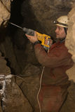 Exploration. Speleologist drilling in Mlynki cave for exploration royalty free stock photography