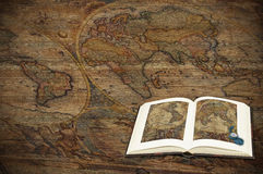 Exploration and discovery. A world map on wood, with geography book Royalty Free Stock Photos
