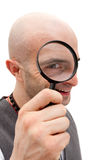 Exploration and discovery. Man exploring with magnifying glass over his eye Royalty Free Stock Photos