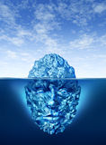 Exploration And Discovery. Concept with an iceberg floating on a blue ocean and the underwater portion of the frozen ice is in the shape of a human head as a Stock Photography