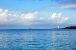 Exploration Lighthouse. Lighthouse in the distance under blue skies and fluffy white clouds Royalty Free Stock Images