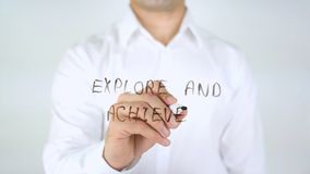 Explore and Achieve, Man Writing on Glass Royalty Free Stock Image