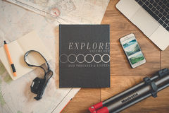 Explore Book Beside Silver Iphone 6 on Brown Wooden Surface Royalty Free Stock Photo