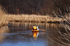 Explore by Canoe. Man canoeing down stream Royalty Free Stock Images