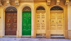 Explore the doors of Valletta, Malta. The facade wall of residential building in South street with a view on four wooden carved doors, Valletta, Malta Stock Photos