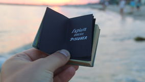 Explore Dream Discover - book with an inscription and the sunset on the beach. Travel book idea. Explore Dream Discover - Inspirational Travel Quote, the stock video
