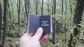 Explore Dream Travel idea. Hand holding a book with the inscription Explore Dream Travel. Beautiful forest in the background stock video
