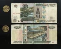 Explore los billetes de banco y las monedas rusas, el anverso y revés de la paridad de diez rublos En un fondo negro imagenes de archivo