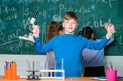 Explore moléculas biológicas Conceito futuro da tecnologia e da ciência Microscópio e tubo de ensaio da posse do menino na escola fotos de stock royalty free