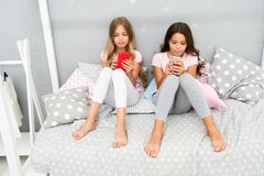 Explore social network. Smartphone for entertainment. Kids play smartphone mobile game application. Smartphone. Application concept. Girlish leisure pajama royalty free stock photos