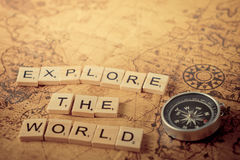 Explore the world concept scrabble text and traveler equipment. On vintage map Stock Photos