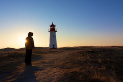 Explorer and a backlit lighthouse Stock Image