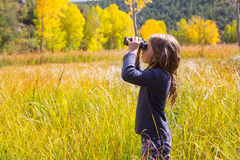 Explorer binocuar kid girl in yellow autumn nature Royalty Free Stock Photography