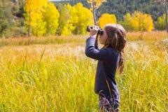 Explorer binocuar kid girl in yellow autumn nature. Explorer binocuar looking kid girl in yellow autumn nature outdoor Royalty Free Stock Photography