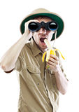 Explorer with binoculars eating banana Stock Image