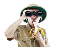 Explorer with binoculars eating banana Stock Images