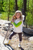 Explorer blond kid girl sith stick and winter white fur Royalty Free Stock Image